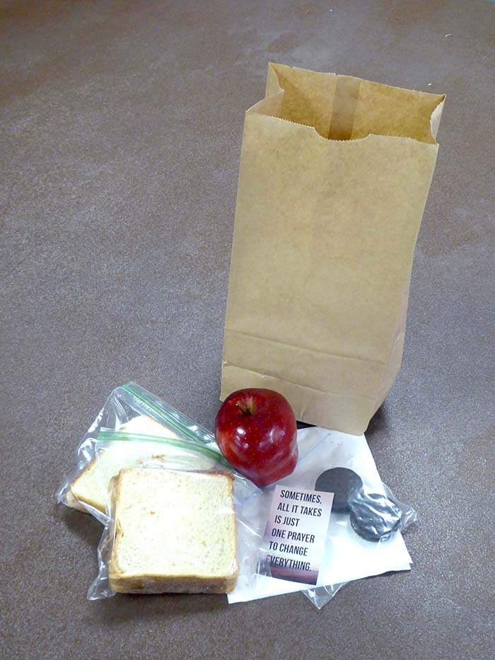 Each bag contains two peanut butter and jelly sandwiches, an apple, cookies, prayer card, bottle of water, and napkins.