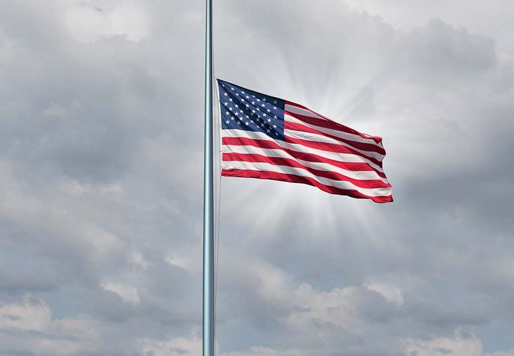 Half mast American flag concept with the symbol of the United States flying at low level on the flagpole or staff on a cloudy day with a sun glow as an icon of honor respect and mourning for fallen heros.